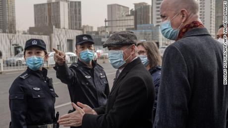 Police ask William Klein (R), acting deputy chief of mission at the US Embassy in Beijing, and Jim Nickel (C),  charge d'affaires of the Canadian embassy in Beijing, to move to another entrance as they stand with other diplomats outside the Beijing No. 2 Intermediate Court on March 22, 2021.