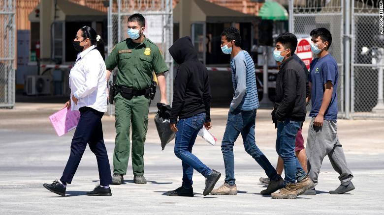 A US Customs and Border Protection agent leads a group of migrants being deported to Reynosa, Mexico, at the McAllen-Hidalgo International Bridge.