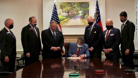 Georgia Gov. Brian Kemp signs SB202 as he sits at a table in a stately room, flanked by six men in suits and before a portrait of what seems to be a painting of an antebellum, plantation-styled home.