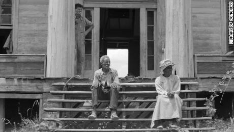 A man and his wife sit on the steps of a plantation house in Greene County, Georgia, in the 1930s.
