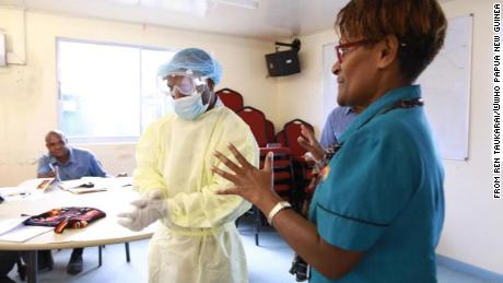 Janlyn Kumbu of PNG's Central Public Health Laboratory trains health workers in Vanimo, West Sepik, on proper PPE procedures.