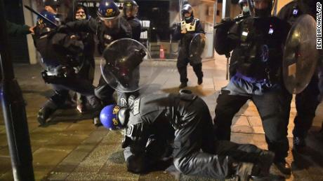Police officers arrest a man as they move over protesters during the