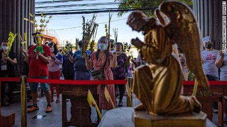 Filipino Catholics wear facemask and face shields carrying Palm Friends as they pray outside a church on 28 March 2021 in Qomon City, Metro Manila, Philippines to celebrate Palm Sunday.