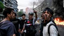 Protesters wearing face paint stand near a burning barricade during an anti-coup demonstration in Yangon, Myanmar, on Tuesday, March 30.