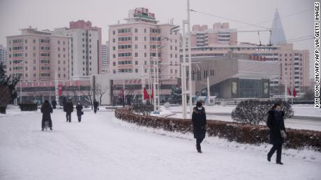 People walk on a snow-covered street near the Arch of Triumph in Pyongyang on January 12.