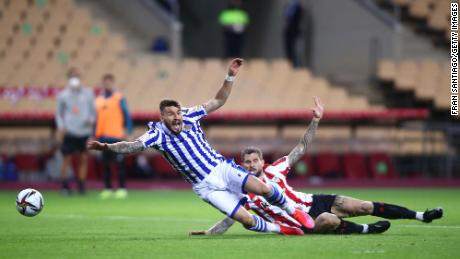 Inigo Martinez of Athletic Bilbao tackles Portu of Real Sociedad which leads to a penalty decision and a red card which was then overturned to a yellow card by VAR during the Copa del Rey final.