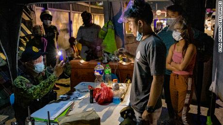 A police officer takes pictures of alleged curfew violators at a quarantine checkpoint on March 29, 2021 in Marikina, Metro Manila, Philippines.