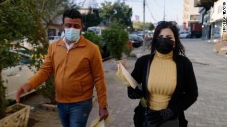 Enass Kareem, right, anti-drug awareness activist, walks through a neighborhood with flyers in central Baghdad.