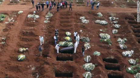 Cemetery workers lower a coffin into a gravesite in Sao Paulo, Brazil on April 7.
