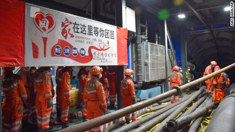 """Rescue workers stand near a banner which reads """"home is waiting for your return"""" at the entrance to a flooded coal mine in Hutubi county in Xinjiang on Sunday."""
