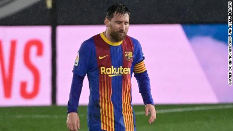 Messi looks on in the pouring rain.