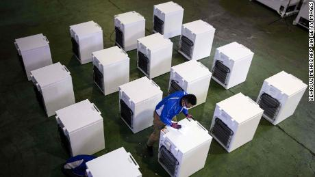 A manager checks deep freezers which will be used to store Covid-19 coronavirus vaccines in Japan.