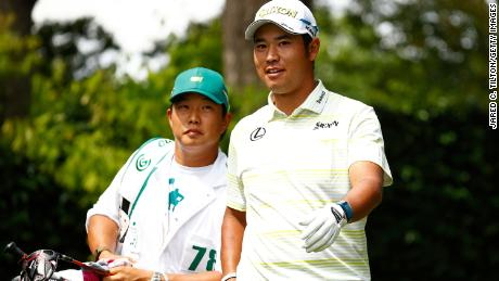 Matsuyama talks with his caddie Shota Hayafuji on the second tee during the final round of the Masters.