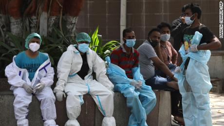 Health workers rest on 19 April in New Delhi, India, amid the last rites of Kovid-19 victims.