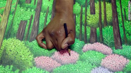 Dixon touches up a golf drawing he is creating in prison.