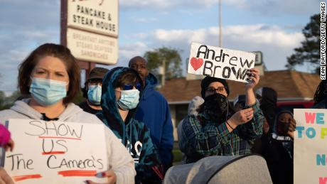 Demonstrators hold signs while participating in a protest march on Thursday in Elizabeth City, North Carolina.