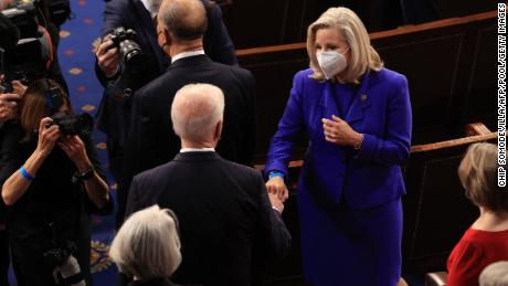 US President Joe Biden (C) greets Rep. Liz Cheney (R-WY) with a fist bump before addressing a joint session of congress in the House chamber of the US Capitol April 28, 2021 in Washington, DC.