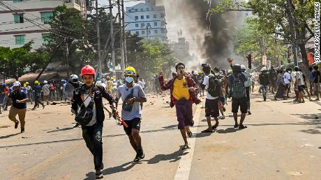 Protesters run as tear gas is fired during a crackdown by security forces on a demonstration against the military coup in Yangon's Thaketa township on March 19.