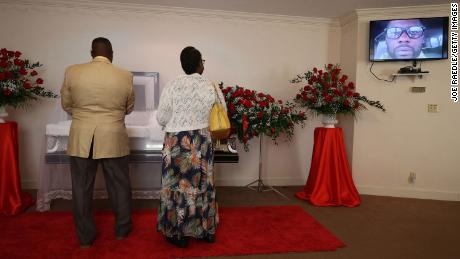 A photograph of Andrew Brown Jr. is displayed on a screen as Edwin Newby and Ella Newby pay their respects to him during a viewing at Horton's Funeral Home and Cremations Chapel on May 2, 2021, in Hertford, North Carolina.