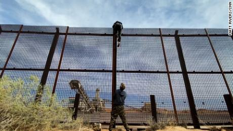 A migrant from Ecuador seen climbing over the US-Mexico border wall fence as a smuggler steadies the ladder below.