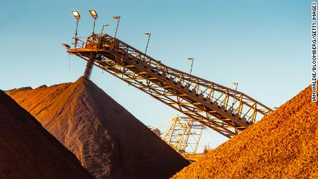 Iron ore falls from a conveyor to a stockpile at the port in Port Hedland, Australia, on Monday, March 18, 2019.