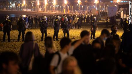 Police officers stand guard as people pack the beach in Barcelona.