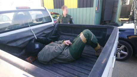 The alleged victim laying on the back of a pick-up truck with his legs and hands bound.