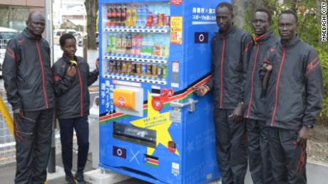 The South Sudan team and their coach, Joseph, (far left) in front of a vending machine in Maebashi city, displaying their nation's flag.