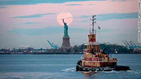 The lovely flower moon from 2020 looms over the Statue of Liberty in New York Harbor.
