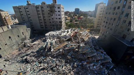 A tower housing the Associated Press, Al Jazeera, and other media offices collapses after Israeli missile strikes in Gaza City, on Saturday, May 15.