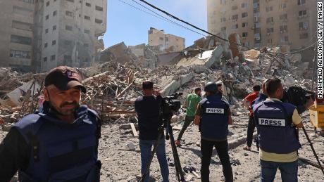Journalists work near the destroyed Al-Jala'a building, which housed international press offices, following an Israeli airstrike in Gaza on Saturday, May 15.