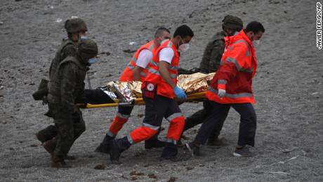 A man is taken on a stretcher by members of the emergency services  and the Spanish army.