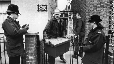 A police investigator walks past a pair of uniformed officers as he carries a large plastic box of evidence from the home of Fred and Rose West at 25 Cromwell Street, Gloucester, England, March 4, 1994.