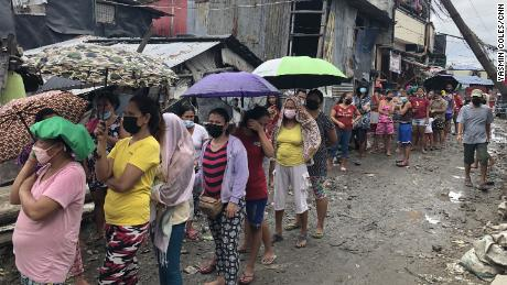 People queue for food at a community kitchen in Manila.