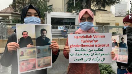 Nuriman Veli, second from left, and her sister protesting the disappearance of their father and his friend, pictured on the placard, outside Istanbul's Saudi consulate on February 12. CNN has blurred a portion of the photo to protect the men's personal details.