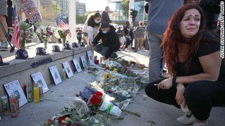 A mourner cries as she looks a a memorial for the nine VTA shooting victims during a vigil at San Jose City Hall.