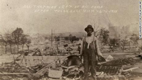 An unidentified man stands alone amid the ruins of what is described as his home in Tulsa, Okla., in the aftermath of the June, 1, 1921, Tulsa Race Massacre.