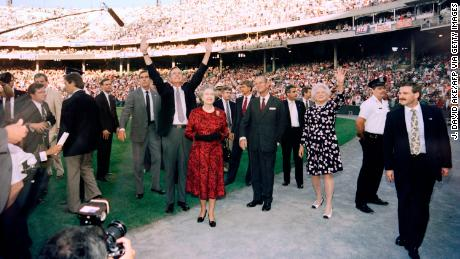 US President George Bush (C), Britain's Queen Elizabeth II (C), Prince Philip, Duke of Edinburgh (4th R) and Barbara Bush (3rd R) wave to the crowd before the start of the Orioles vs. the Oakland Athletics baseball game at the Memorial Stadium in Baltimore on May 15, 1991.