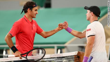 Federer shakes hands with German Koepfer after winning the game early Sunday morning.
