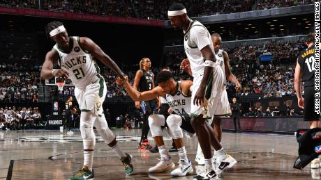 Jrue Holiday and Bobby Portis of the Bucks help Antetokounmpo during their game against the Nets.