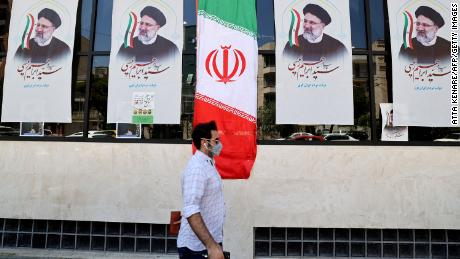 An Iranian man walks by posters of Raisi outside a campaign office in Tehran on June 7.