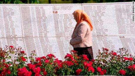 A woman looks at the names of the victims of the Srebrenica massacre at the memorial cemetery in Potokari, near eastern Bosnia, Tuesday, June 8.