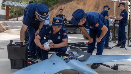 Workers prepare a drone to monitor migratory wild Asian elephants in Ishan County, Yuxi City in southwest China's Yunnan province, on May 29.