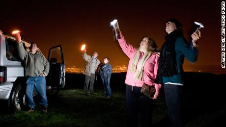 UFO spotters use flashlights to look for stars and aliens in the night sky in South Wales, Australia, in 2008.