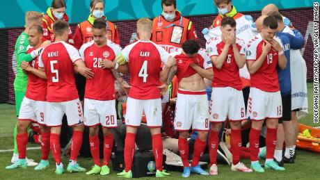 Danish players gather as paramedics with midfielder Christian Eriksson (not seen) during Saturday's match.