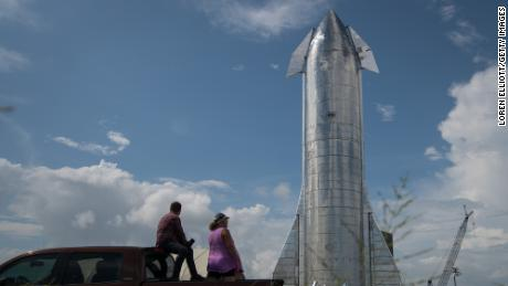 Space enthusiasts look at a prototype of SpaceX's Starship spacecraft at the company's Texas launch facility on September 28, 2019 in Boca Chica near Brownsville, Texas. The Starship spacecraft is a massive vehicle meant to take people to the Moon, Mars, and beyond. (Photo by Loren Elliott/Getty Images)