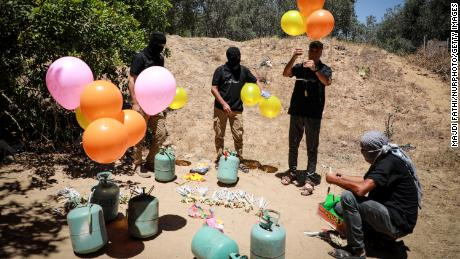 Militants east of Gaza City prepare incendiary balloons to launch across the border fence towards Israel on Wednesday.