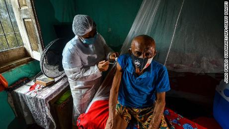 A man is vaccinated against Covid-19 by a health worker in a remote area of Moju, Para state, Brazil on April 16, 2021.