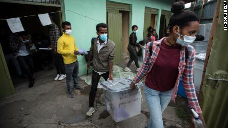 Electoral workers carry ballot boxes in the rain from a distribution center in Addis Ababa, Ethiopia on June 20.