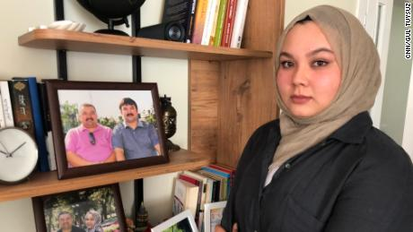 Dilsar Ablimit, 21, at her home in Turkey in June, with a photo of her father and uncle before they were detained.